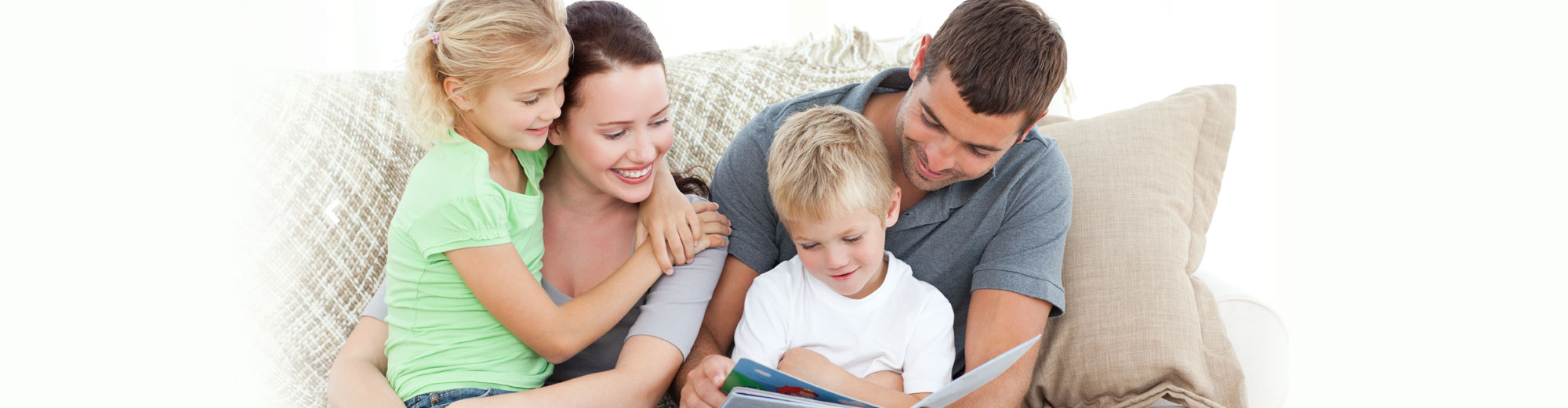 Happy family reading a book on couch